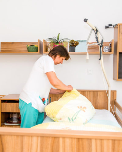 Caregiver In The Retirement Home Changing And Cleaning Seniors Bedroom